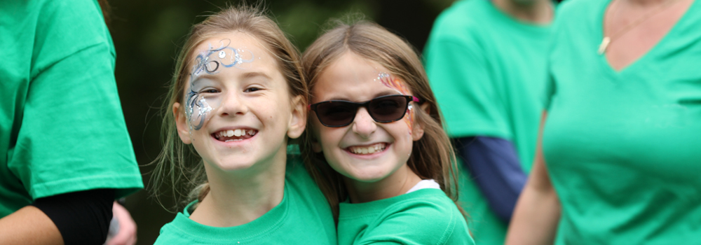 two girls smiling wearing green shirts